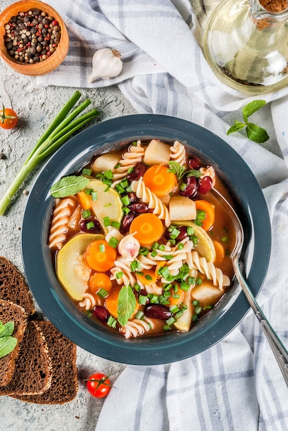 フジッリパスタ、ベジタリアン料理のコンセプトとイタリアの野菜スープミネストローネ Premium写真