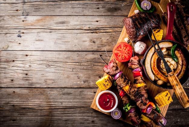 各種バーベキューフードグリル肉、バーベキューパーティーフェスト-シシカバブ、ソーセージ、肉の切り身、新鮮な野菜、ソース、スパイス、古い木製の素朴なテーブル Premium写真