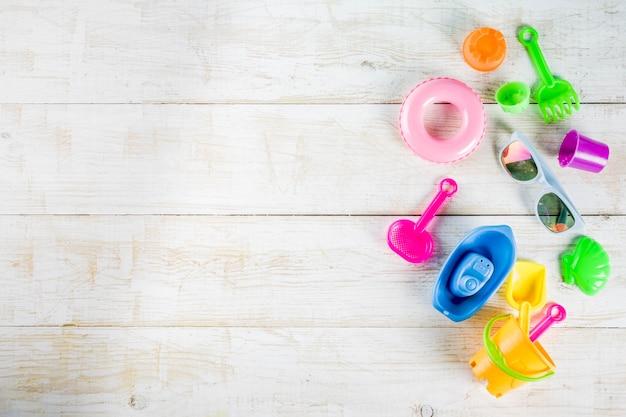 Концепция летних каникул с пластиковыми пляжными детскими игрушками - ведро, совок, грабли, плесень лодка, спасательный круг игрушки белый деревянный стол Premium Фотографии