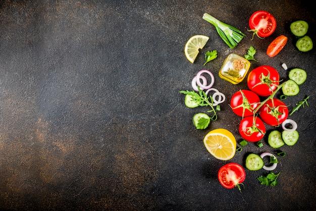 調理台、新鮮なサラダの材料、イタリア料理-トマト、オリーブオイル、レモン、きゅうり、ルッコラ、パセリ、玉ねぎ、暗いさびたテーブルトップビュー Premium写真
