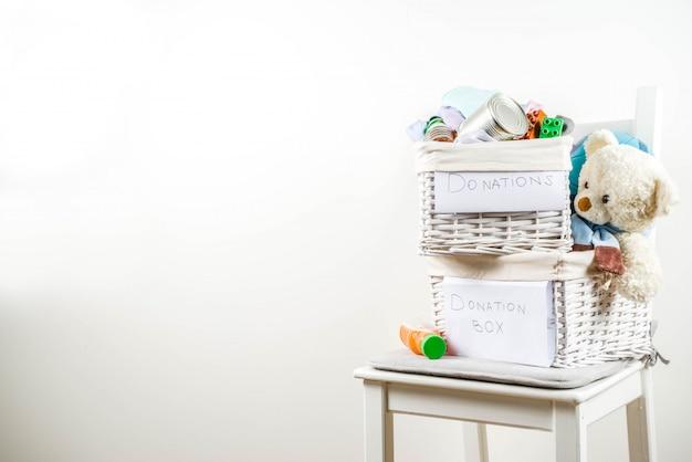 服、おもちゃ、食べ物が入った募金箱 Premium写真