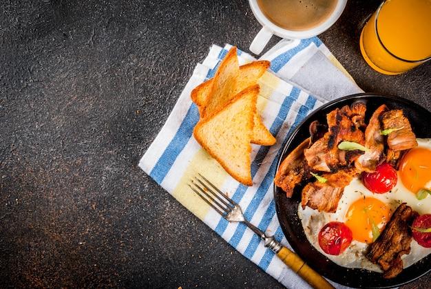 伝統的な自家製イングリッシュアメリカンの朝食、目玉焼き、トースト、ベーコン、コーヒーマグカップ Premium写真