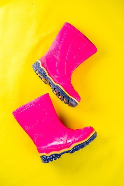 秋の子供布コンセプト、雨のための明るいピンクのゴム長靴 Premium写真