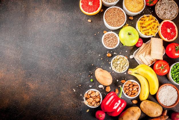 ダイエット食品の背景概念、健康的な炭水化物(炭水化物)製品-果物、野菜、穀物、ナッツ、豆、暗い青色のコンクリート背景平面図コピースペース Premium写真