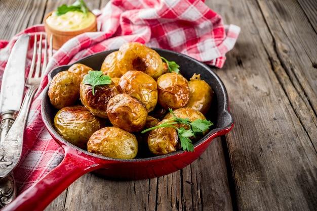 フライパン全体の若いジャガイモ、自家製のベジタリアン料理、木製の古い素朴なテーブル、ソース、コピースペースで焼いた Premium写真