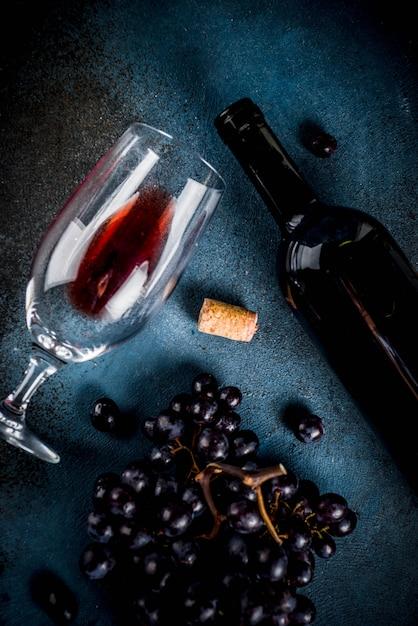 ガラスとブドウの赤ワインのボトル Premium写真