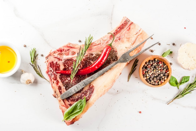 生の牛肉の霜降り肉ストリップロンリブアイステーキとスパイス Premium写真