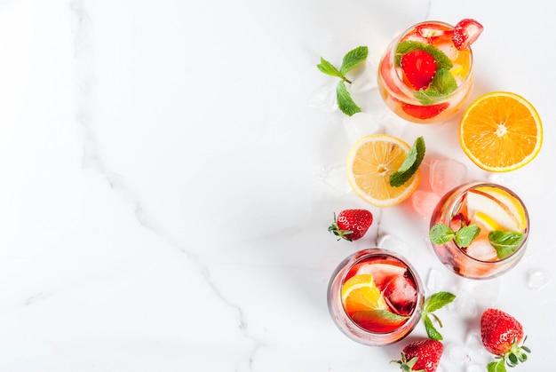 新鮮なフルーツ、ベリー、ミン入りの冷たい白、ピンク、赤のサングリアカクテル Premium写真