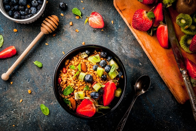 ミューズリーまたはグラノーラとナッツ、新鮮なベリー、フルーツのヘルシーな朝食 Premium写真