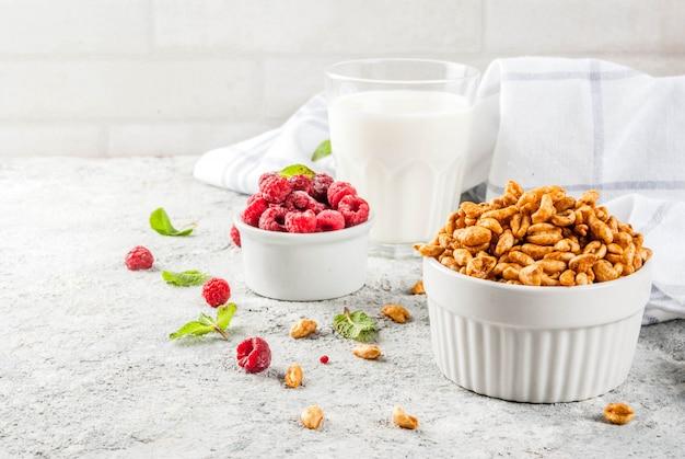 健康的な朝食の食材。朝食用シリアル、ミルクまたはヨーグルトのグラス、ラズベリー Premium写真
