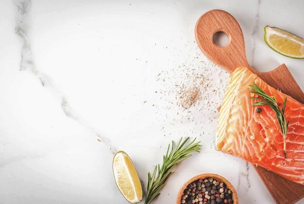 新鮮な生の魚サーモン、ステーキの切り身、スパイス、ライム、ローズマリー、塩 Premium写真