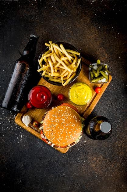 Разнообразная еда для вечеринок, гамбургеры, картофель фри, картофельные чипсы, маринованные огурцы, лук, помидоры и бутылки холодного пива Premium Фотографии