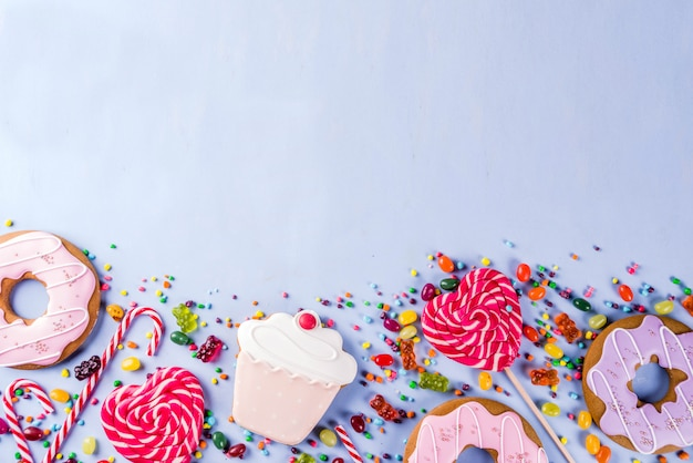 お菓子の創造的なレイアウト、ロリポップ、ゼリー、キャンディ、クッキードーナツ、カップケーキのデザートコンセプト Premium写真