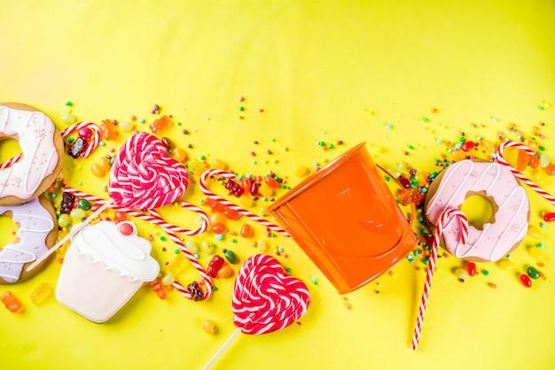 ハロウィーンのお菓子のコンセプト、お祝いカボチャの形のバケツ、お菓子やキャンディーでいっぱい Premium写真