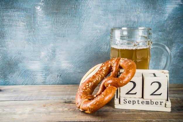 ビールガラスマグカップ、プレッツェル、古いレトロなスタイルの木製カレンダーオクトーバーフェストのお祝いのコンセプト Premium写真