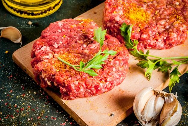Котлеты из сырого бургера с солью, перцем, маслом, зеленью и специями Premium Фотографии