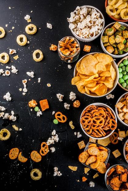 さまざまな不健康なスナッククラッカー、甘い塩味のポップコーン、トルティーヤ、ナッツ、ストロー、ブレツェル Premium写真