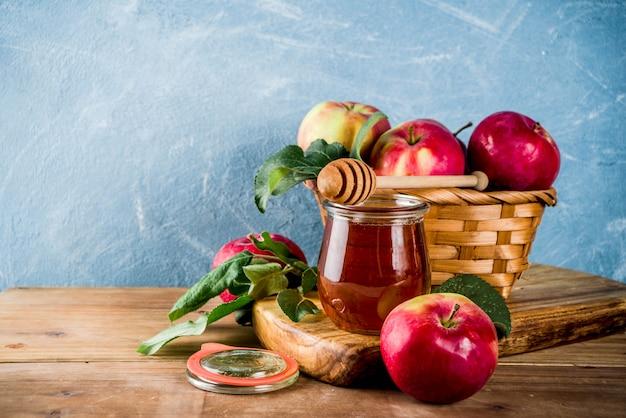 Еврейский праздник рош ха-шана или концепция яблочного праздника, с красными яблоками, яблочными листьями и медом в банке Premium Фотографии
