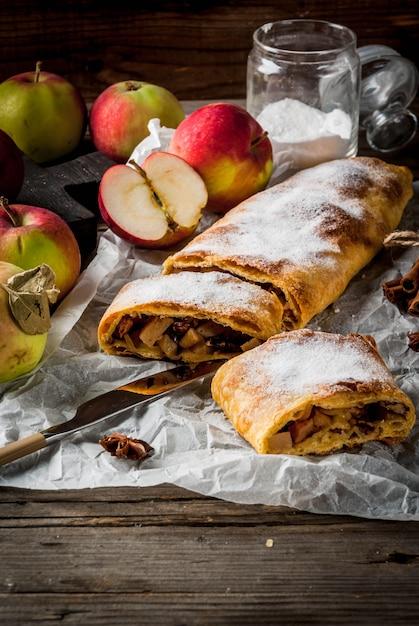 ホーム秋、夏のベーキング、パイ生地。ナッツ、レーズン、シナモン、粉砂糖入りのリンゴのシュトルーデル Premium写真