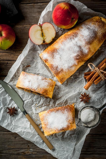 ナッツ、レーズン、シナモン、粉砂糖入りのリンゴのシュトルーデル Premium写真