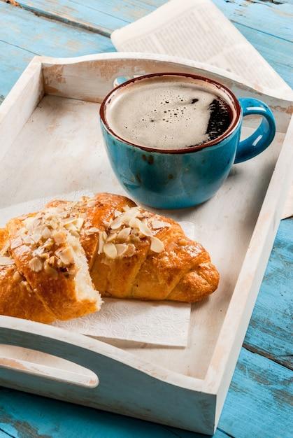 Большая кофейная кружка, круассан и газета Premium Фотографии