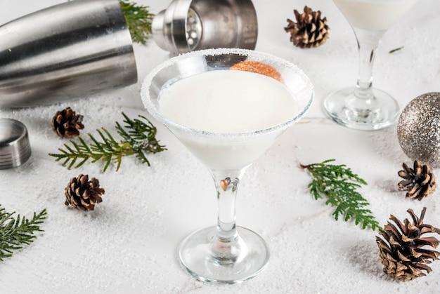 クリスマスの飲み物のアイデアとレシピ。ホワイトチョコレートスノーフレークマティーニカクテル Premium写真