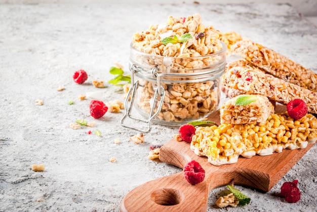 健康的な朝食とスナックのコンセプト自家製グラノーラ、新鮮なラズベリーの瓶とナッツ、グラノーラバー、グレーストーンストーンバックグラウンド Premium写真