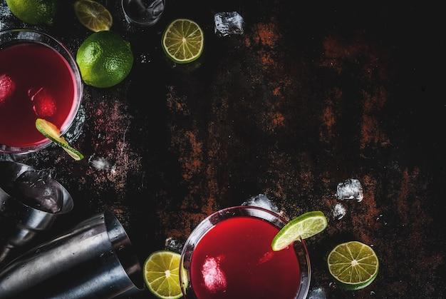 Красный космополитичный коктейль с лаймом в бокале для мартини на темном ржавом фоне Premium Фотографии