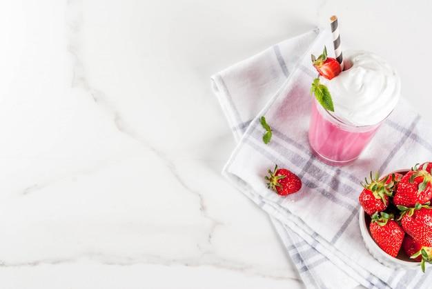 新鮮なベリーと白い大理石の背景にミントの冷たいいちごのミルクセーキトップビュー Premium写真