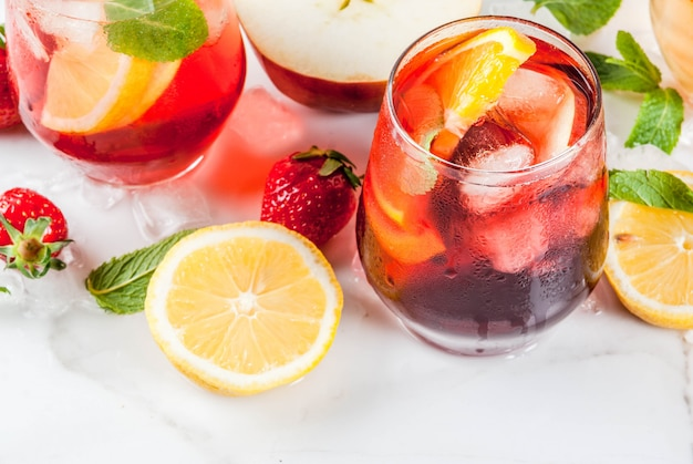 Холодные белые розовые и красные сангрия коктейли со свежими фруктами, ягодами и мятой. Premium Фотографии
