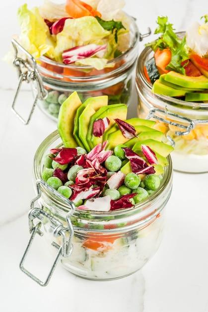 新鮮な野菜と白い大理石のテーブルに健康的なドレッシングの瓶に新鮮なサラダ Premium写真