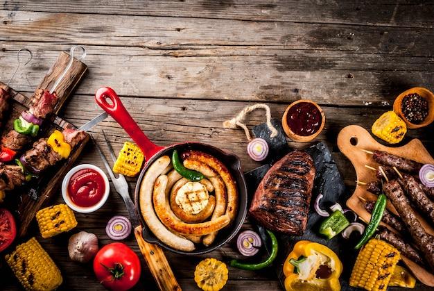 各種バーベキューフードグリル肉、バーベキューパーティーフェスト-シシカバブ、ソーセージ、焼き肉の切り身、新鮮な野菜、ソース Premium写真