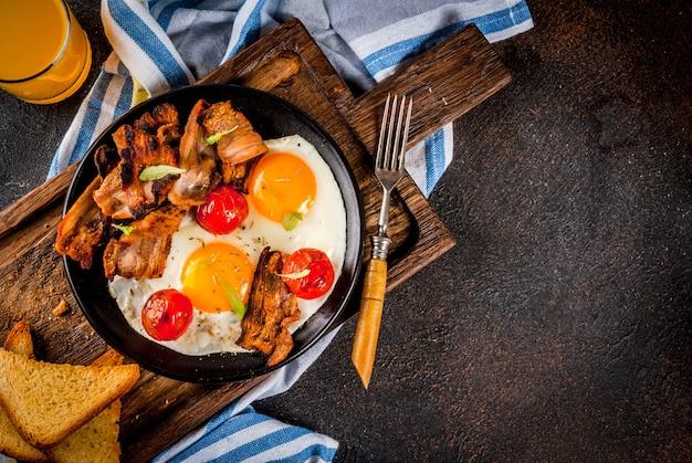 伝統的な自家製イングリッシュアメリカンの朝食、目玉焼き、トースト、ベーコン、コーヒーマグカップとオレンジジュース暗い背景、トップビューコピースペース Premium写真