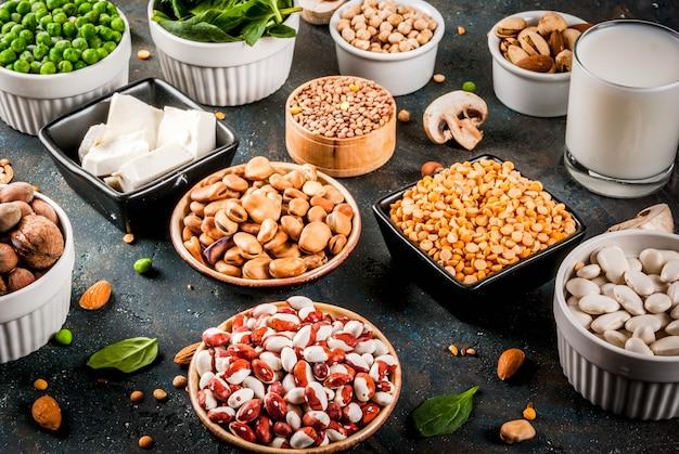 Здоровая диета, веганская пища, источники растительного белка: тофу, веганское молоко, бобы, чечевица, орехи, соевое молоко, шпинат и семена. вид сверху на белом столе. Premium Фотографии