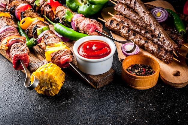 Ассорти из различных блюд барбекю, приготовленных на гриле, мясо, барбекю-вечеринка - шашлык, сосиски, филе мяса на гриле, свежие овощи, соусы, специи, стол из темного ржавого бетона, пространство над копией Premium Фотографии