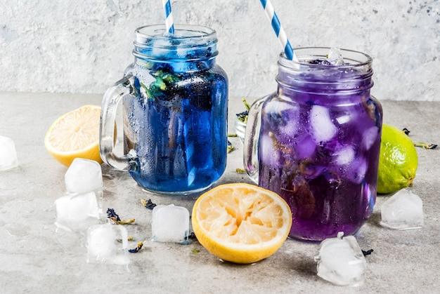 健康的な夏の冷たい飲み物、アイスオーガニックの青と紫の蝶エンドウ豆の花茶、ライムとレモン添え Premium写真