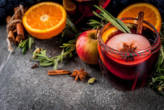 Традиционные зимние и осенние напитки коктейли на рождество и на день благодарения глинтвейн с апельсиновым яблоком, розмарином, корицей и специями на темном каменном фоне Premium Фотографии