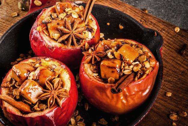 秋の料理のレシピグラノーラタフィーとスパイスをフライパンに詰めた焼きりんご Premium写真