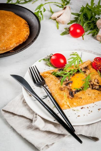 フランス料理朝食ランチスナックビーガンフード伝統料理ガレットサラシン卵入りクレープチーズ炒めマッシュルームルッコラの葉とトマト Premium写真