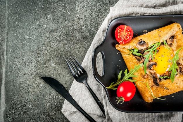 フランス料理朝食ランチスナックビーガンフード伝統料理ガレットサラシン卵入りクレープチーズ炒めマッシュルームルッコラの葉とトマト黒い石のテーブル Premium写真