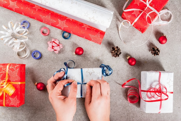 クリスマス休暇の準備。テーブルの上の贈り物や飾り、写真の女の子の手は贈り物のリボンを結びます。上面図 Premium写真