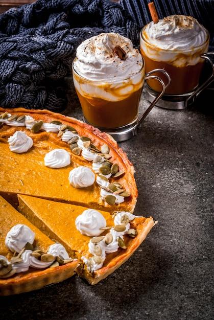 伝統的な秋の食べ物のセット。ハロウィーン、感謝祭。スパイシーなカボチャのラテ、カボチャのパイ、ホイップクリームとカボチャの種のタルタレット、カボチャのスープ、黒い石のテーブルの上。コピースペース Premium写真