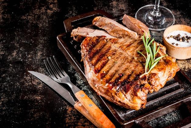 グリル鍋ボードにスパイスと牛肉のグリルステーキ、赤ワイングラス。コピースペース Premium写真