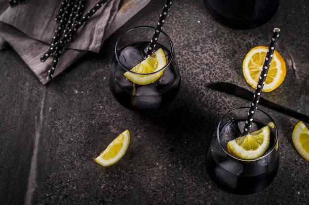 トレンディな食品夏の飲み物ドリンクデトックスとダイエットの概念炭アイスレモンジュースとレモンと黒レモネード Premium写真