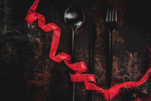 赤いリボンと暗いさびた表面に銀器のセット Premium写真