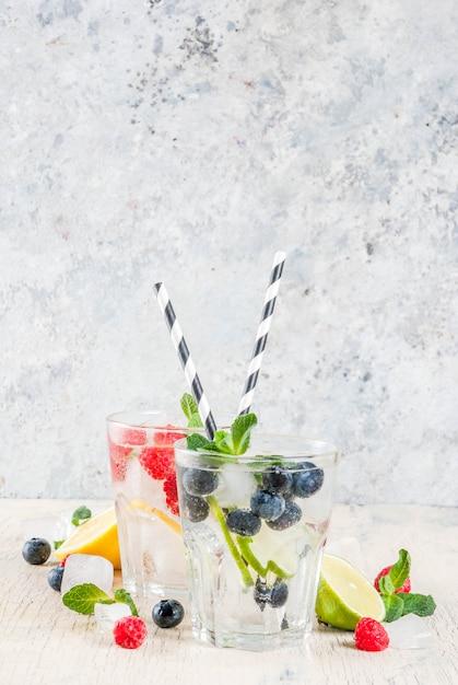 さまざまなベリーレモネードやモヒートカクテル新鮮なアイスレモンライムラズベリーブルーベリー注入水夏健康的なデトックスドリンク明るい背景 Premium写真
