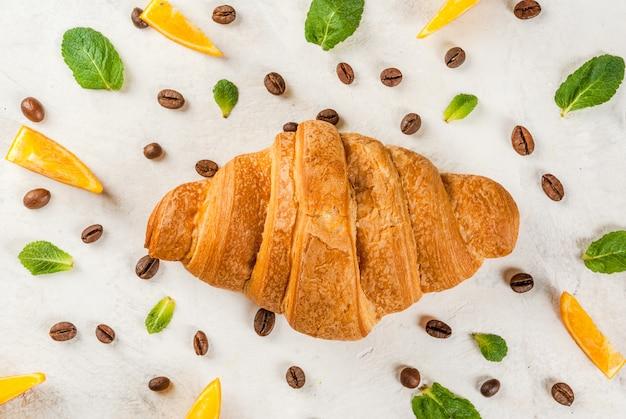 Круассан с кофейными зернами, апельсинами и листьями мяты Premium Фотографии