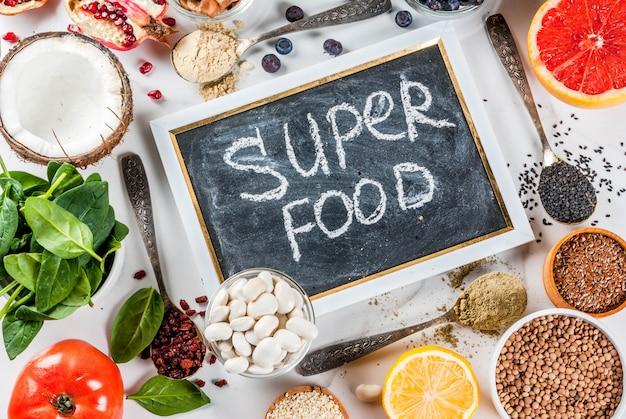 Набор органических здоровой диеты суперпродуктов - бобы бобовые орехи семена зелень фрукты и овощи на белом фоне Premium Фотографии
