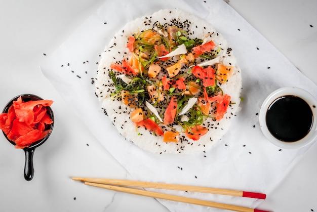 Суши-пицца с лососем, хаяси вакамэ, дайкон, маринованный имбирь, красная икра. Premium Фотографии