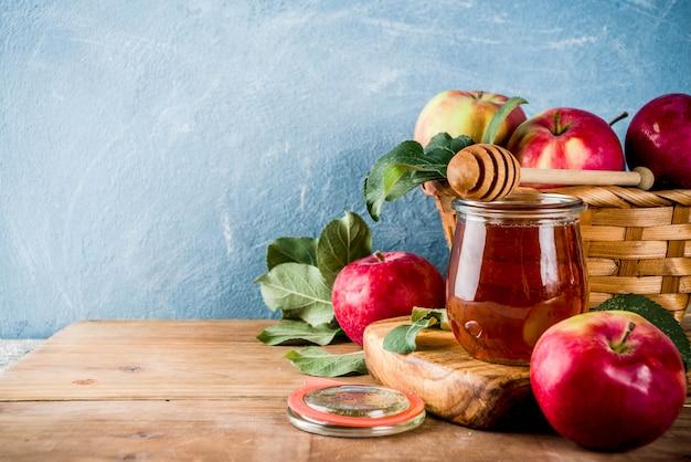 Еврейский праздник рош ха-шана или концепция яблочного праздника, с красными яблоками, яблочными листьями и медом в банке, голубой и деревянный фон Premium Фотографии
